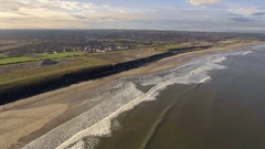 Aerial view forward motion overlooking UK coastline with town in the background Stock Footage