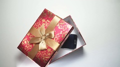 Smartphone In Red Gift Box On White Background. 4K Stock Footage