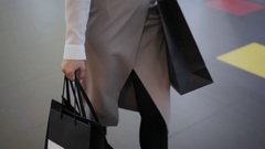 Female hands holding a shopping bags close up in mall center Stock Footage