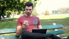 Man looking occupied while using laptop and checking something on smartphone Stock Footage