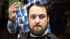 Barber making haircut of attractive bearded man in barbershop Stock Footage