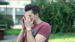 Man looking morose while having a headache in the park Stock Footage