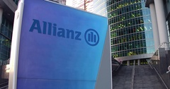 Street signage board with Allianz logo. Modern office center skyscraper and Stock Footage