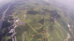Skydiver parachuting above green fields. River. Extreme activity. Adrenaline Stock Footage