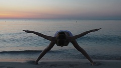 Girl practices yoga near the sea Stock Footage