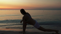 Slim athletic girl in silhouette practicing yoga overlooking the beach Stock Footage