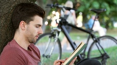 Man looking absorbed while reading book under the tree Stock Footage