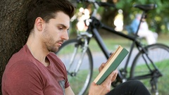 Man receives message while reading book under the tree Stock Footage