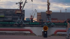 Cargo port at seafront. Cranes. Containers. Men on rollers skaters jump on pipe Stock Footage