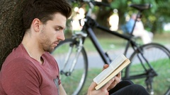 Man doing serious look to the camera while sitting in the park and reading book Stock Footage