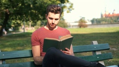 Man receives message on smartphone while reading book in the park Stock Footage