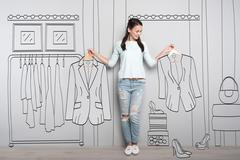 Happy woman holding clothes on hangers Stock Photos