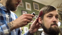 Portrait of a bearded barber giving a haircut to his client with comb and Stock Footage