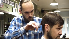 Concentrated Barber cutting hair with electric razor in barber shop Stock Footage