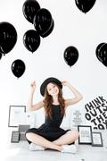 Cheerul beautiful young woman sitting and holding black balloons Stock Photos