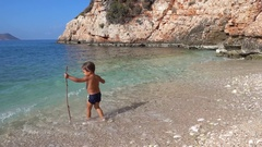 Kid with a stick enters the sea to fish Stock Footage