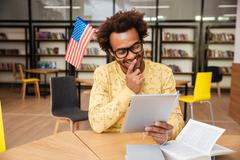 Cheerful man with american flag and tablet joking in library Stock Photos