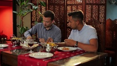Men are eating in the indian restaurant Stock Footage