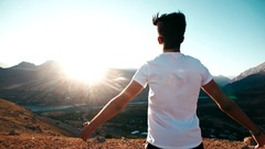 Young Asian male reaching to the top of the mountain area, standing on top of Stock Footage