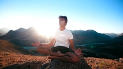 Young Asian man doing yoga in the highlands, Lotus position, healthy life, sun Stock Footage