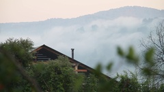 The roof of a wooden house. Village. Fog. Clouds. Mountain. Russian Siberia. Stock Footage