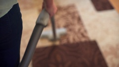 Woman using vacuum cleaner on rug at home in the living room Stock Footage