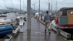 Man Walking along Harbor Docks Amidst Fishing Boats Stock Footage
