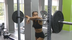 Portrait of young woman prepares to lift heavy barbells at the gym Stock Footage