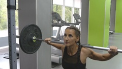 Oung woman holding a barbell with heavy weights on her shoulders as she squats Stock Footage
