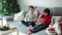 Two cute children, eating chocolate santa at home Stock Footage
