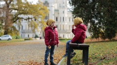 Two beautiful children, boy brothers, sitting on bench in beautiful renaissance  Stock Footage
