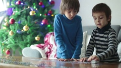Two sweet children, collect puzzles at home on Christmas Stock Footage