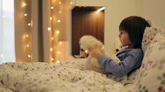 Cute sick child, boy, staying in bed, playing with teddy bear Stock Footage