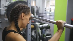 Portrait of young woman prepares to lift heavy barbells at the gym. Slow motion Stock Footage