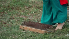 Men stand on the board with nails. Slow motion Stock Footage
