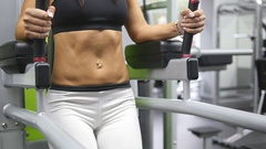 Young strong woman with perfect fitness body exercising abdominals in gym Stock Footage