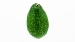 Green avocado suspended in the air rotates in loop     Stock Footage