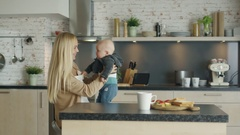 Young Mother Nursing Her Laughing Child while Standing on the Kitchen. Stock Footage