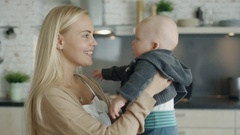 Young Mother Holds and Plays with Her Baby while Standing on the Kitchen Stock Footage