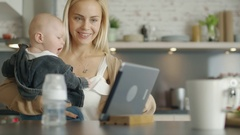 On the Kitchen Mother Holds Her Baby. Both Look at Screen. Stock Footage