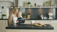 Beautiful Mother Holds Child in Her Hands on the Kitchen.  Stock Footage