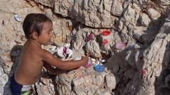 Cute artful boy paints rocks Stock Footage