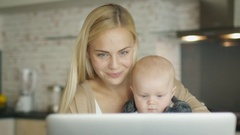 While Sitting on the Kitchen before Laptop Smiling Mother Holds Baby Stock Footage