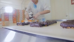 Worker's hands packing eclairs in boxes. Eclairs moving on automated belt Stock Footage