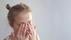 Young woman rubs her eyes Stock Footage