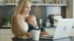 On the Kitchen Beautiful Smiling Mother Uses Laptop While Holding Adorable Child Stock Footage