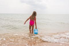 Five-year girl picking up a bucket of water in the sea Stock Photos