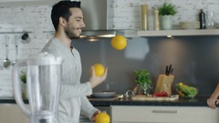 Lively Young Man Impresses His Girlfriend by Juggling Oranges on the Kitchen. Stock Footage