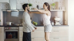Happy Couple on the Kitchen. Girl Jumps into Guy's Arms. Stock Footage