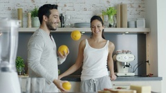 Slow Motion of a Guy Impressing His Lady with Juggling Oranges on the Kitchen. Stock Footage